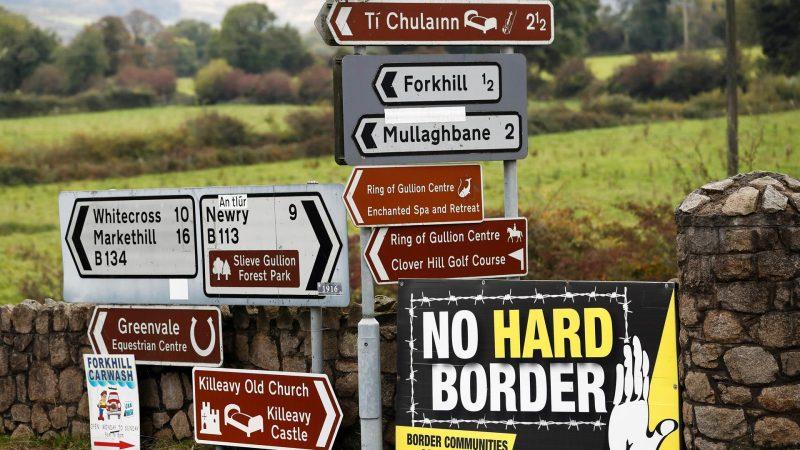 Alt=Una pancarta (dcha.) contra la frontera dura entre Irlanda del Norte y la República de Irlanda rodeada de carteles indicativos en la localidad norirlandesa de Forkhill. EFE/Javier Etxezarreta/Archivo
