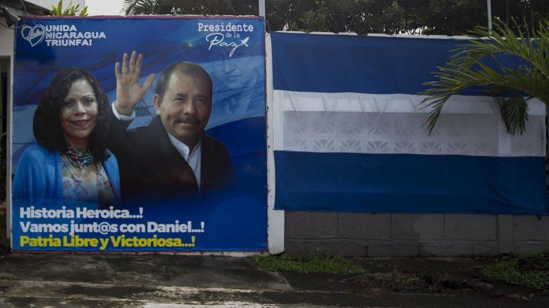 Alt = Pancarta política con la imagen de la fórmula presidencial del presidente de Nicaragua, Daniel Ortega (d), y la vicepresidenta, Rosario Murillo (i), junto a una bandera de Nicaragua en Managua (Nicaragua). EFE/Jorge Torres